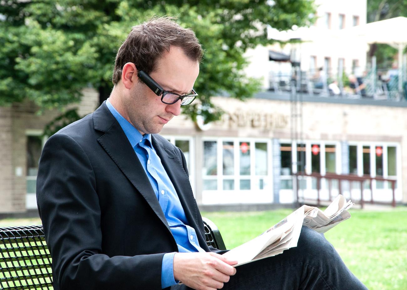 Hombre leyendo el periódico con las gafas OrCam My Eye.