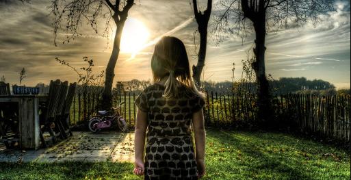 Niña vista de espaldas delante de un jardín