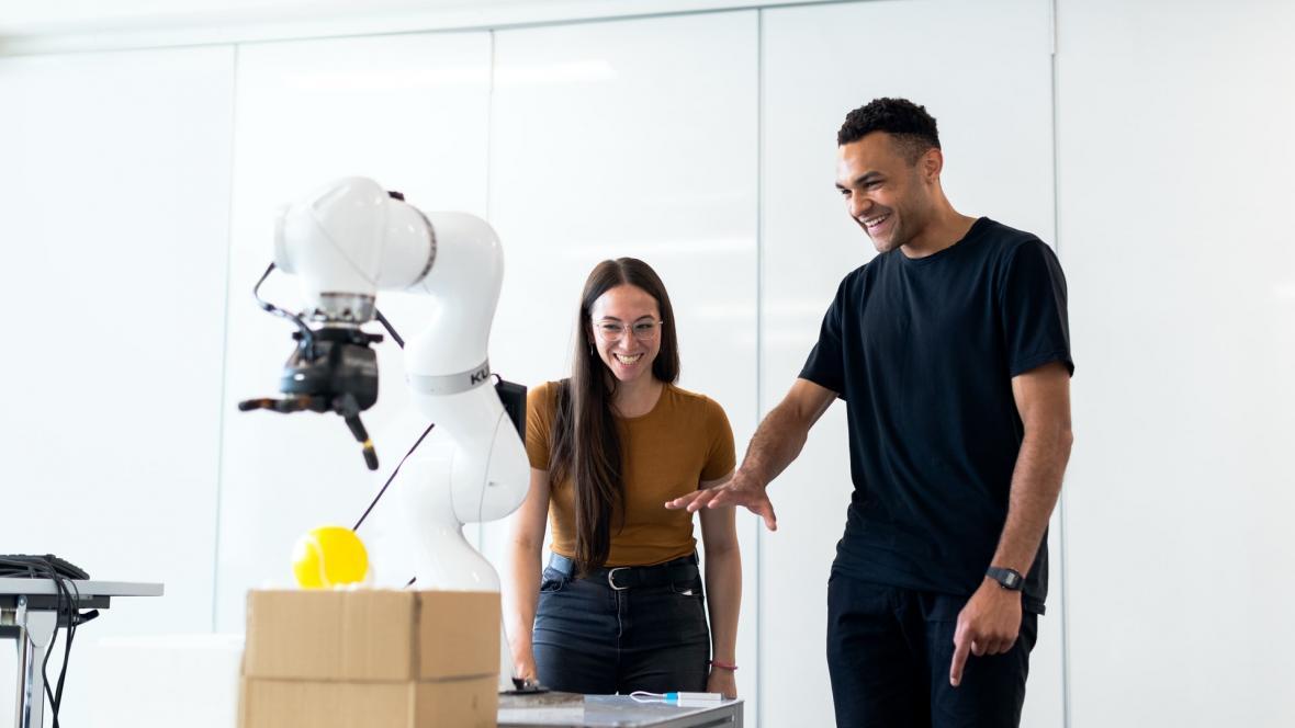 Dos personas delante de una mano robótica.