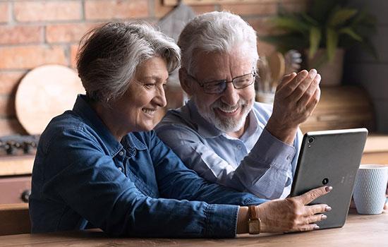 Pareja de personas mayores delante de un ordenador portátil
