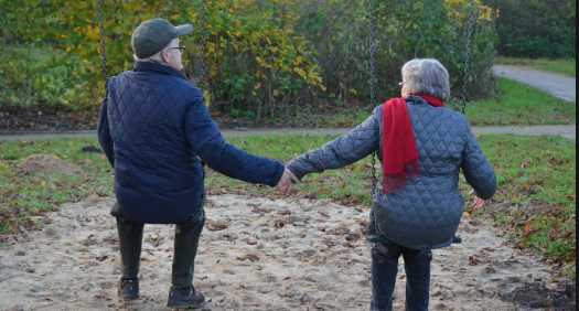 Un hombre y una mujer mayores de espalda cogidos de la mano pasean.