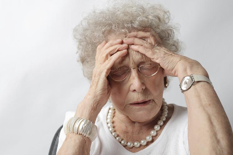 Señora mayor con las manos en la cabeza y con expresión de malestar.