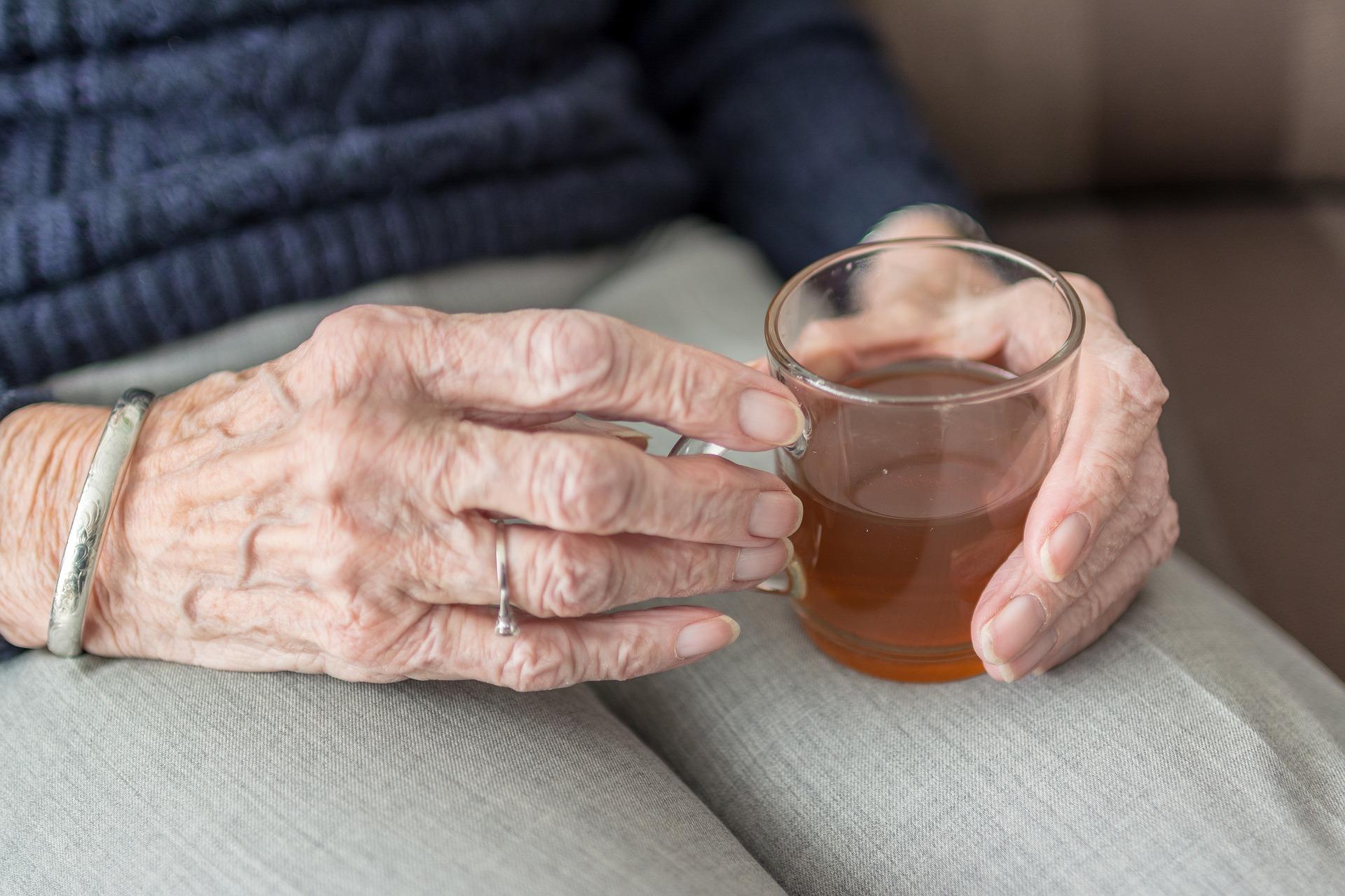 manos de una persona mayor que sujeta una taza de agua