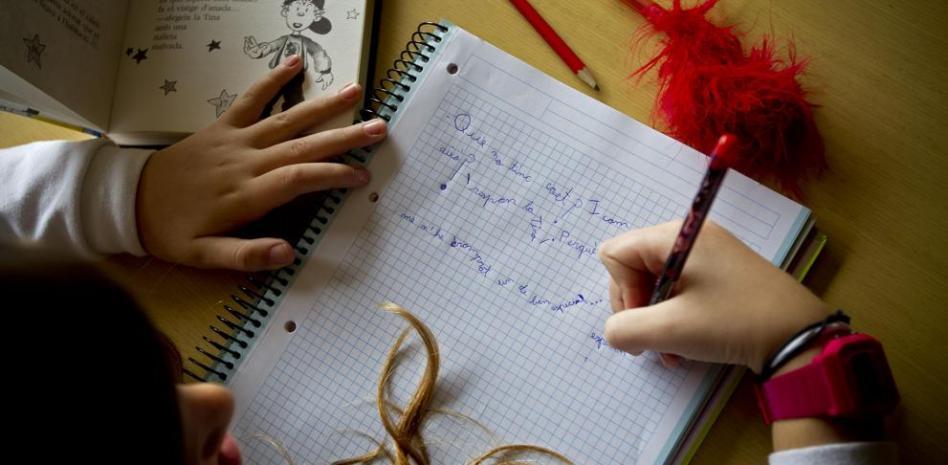 primer plano de un cuaderno con una niña que escribe en él.